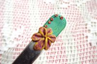 ručně modelovaná lžička s medovou kytičkou na zeleném podkladyu