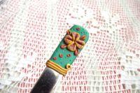 3. ručně modelovaná lžička s medovým květem na zeleném podkladu