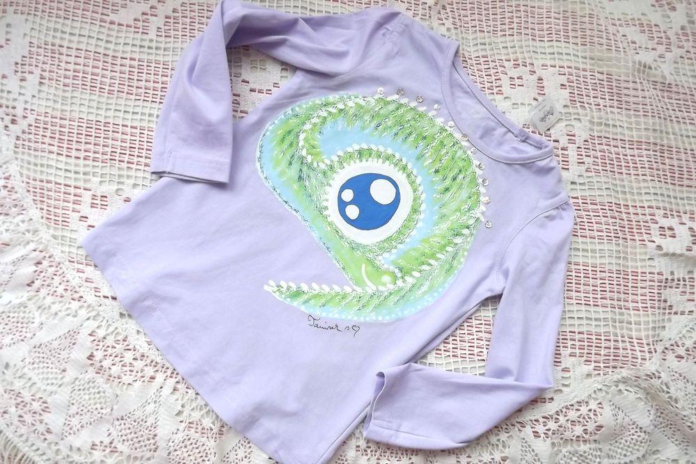 Světle fialové tričko s dlouhým rukávem a ručně namalovaným drakem. Drak je pošitý flitry, velikost 92