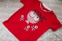 Veselý pirát namalovaný na červeném tričku s krátkým rukávem a vrstveným efektem, kolem piráta jsou lebčičky se zkříženými hnáty. veliksot 128