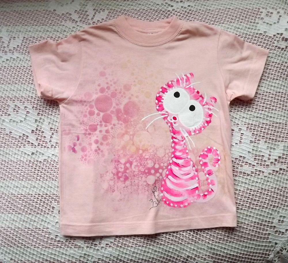 Jemná růžovobílá kočička zahalená jemným růžovozlatým třpytivým závojem - na růžovém bavlněném tričku s krátkými rukávy. velikost 116