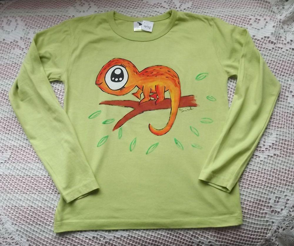 Veselý oranžový chameleon na větvi je namalovaný na zeleném bavlněném tričku s dlouhým rukávem velikost 140