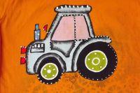 modrý malovaný traktor na oranžovém tričku 122 detail